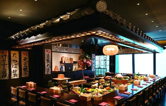 寿司店沉静清新的设计风格,在色彩的搭配上非常和谐,吊顶采用黑白相间错层的设计,一侧为长方形,一侧为圆形,将房间的层次感表现出来,吊顶下方的墙壁采用了木条形的设计,带给我们一种延伸的感觉,黑与绿搭配的卡座,舒适温馨,长方形的吧台,中间为透明的玻璃,将通透的感觉表现出来。      寿司店大气通透的设计风格,长方形中空的吧台营造出一种温馨的氛围,吧台采用了高低不同的设计,配以木质的椅子,自然精致,透明的玻璃增强了房间的通透感,吊顶采用了黑白相间的搭配,圆形下垂式的吊顶,将房间的层次感打造出来。      装